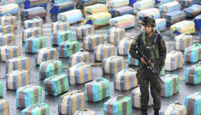 A Colombian police officer stands guard near packs of confiscated marijuana in Cali
